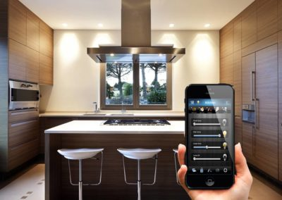 smartphone with home automation software in front of smart kitchen
